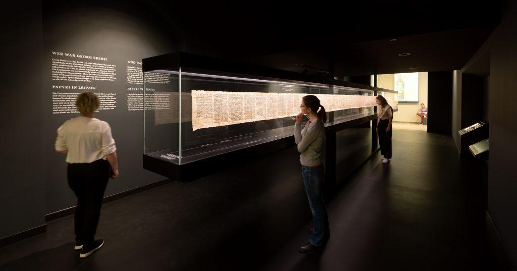 Gäste betrachten die Replik des Papyrus Ebers.