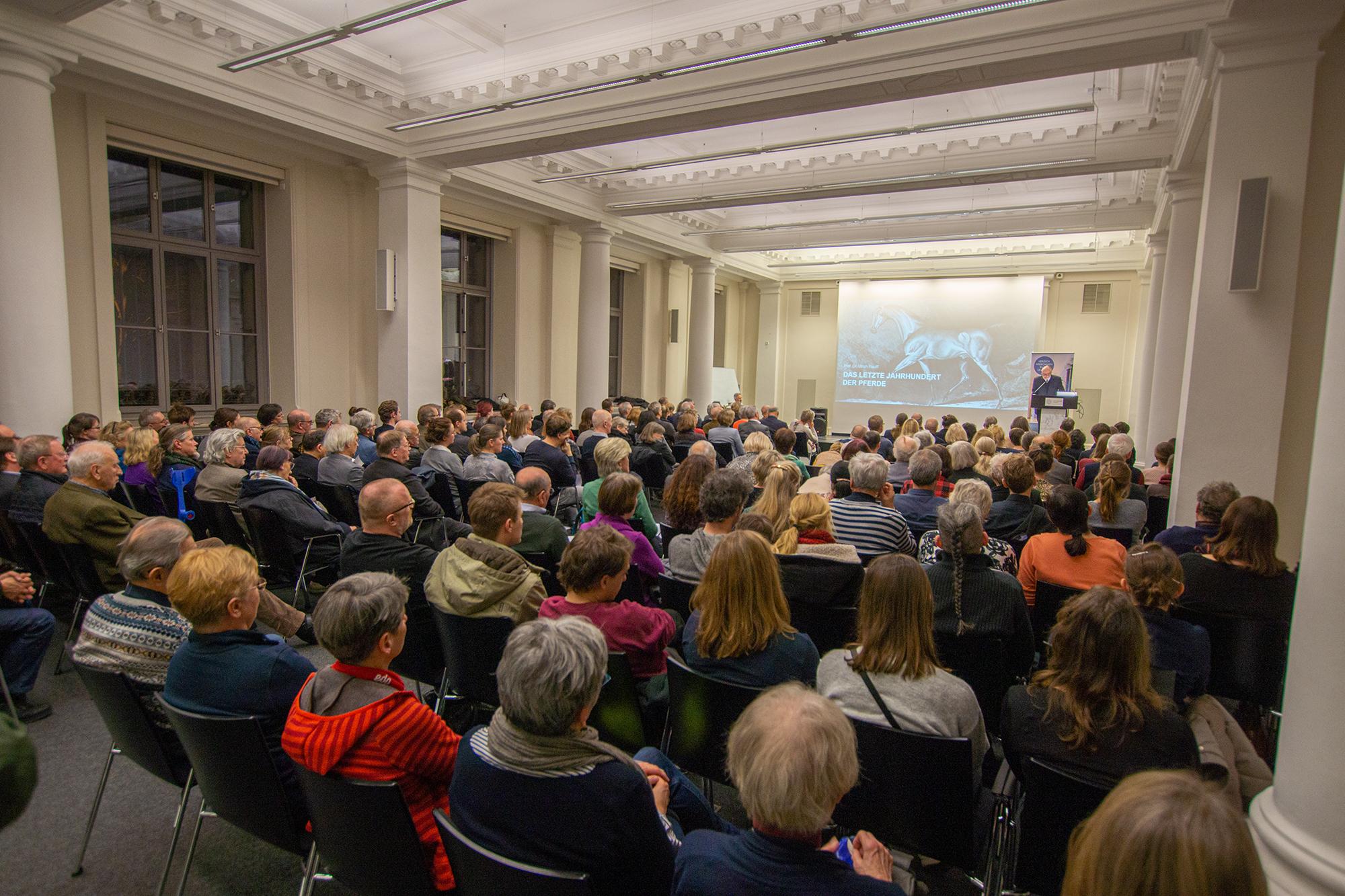 Ein Publikum sitzt im Vortragssaal der Albertina und hört einen Vortrag
