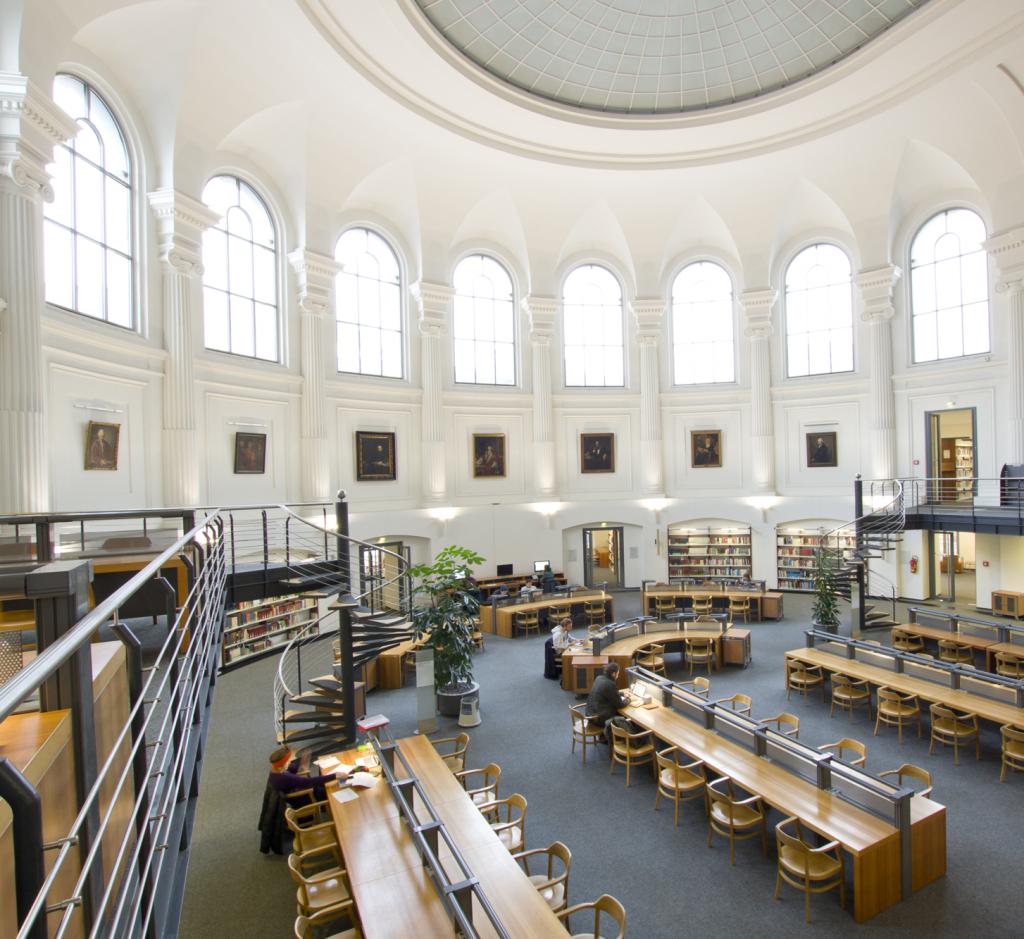 Ein runder Lesesaal mit vielen Sitzgelegenheiten, hell erleuchtet durch große Fenster.