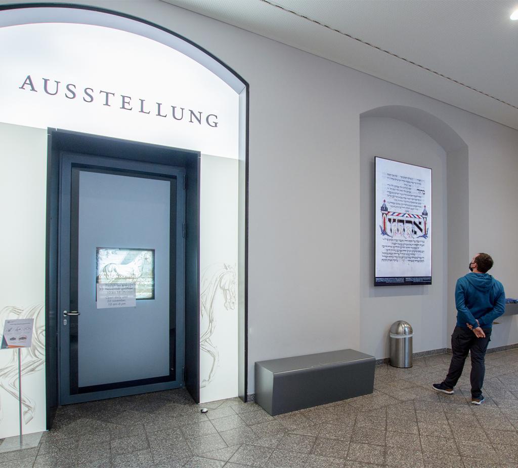 """Eine Tür im Foyer mit dem Schriftzug """"Ausstellung"""" darüber. Daneben ein Mann, der die Dauerausstellung besichtigt."""