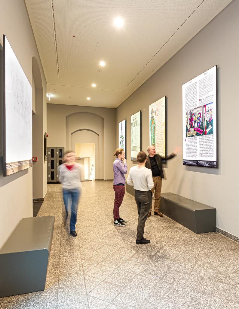Der Direktor der UB Leipzig erläutert einer kleinen Gruppe eine Replik der Dauerausstellung im Foyer der Albertina.
