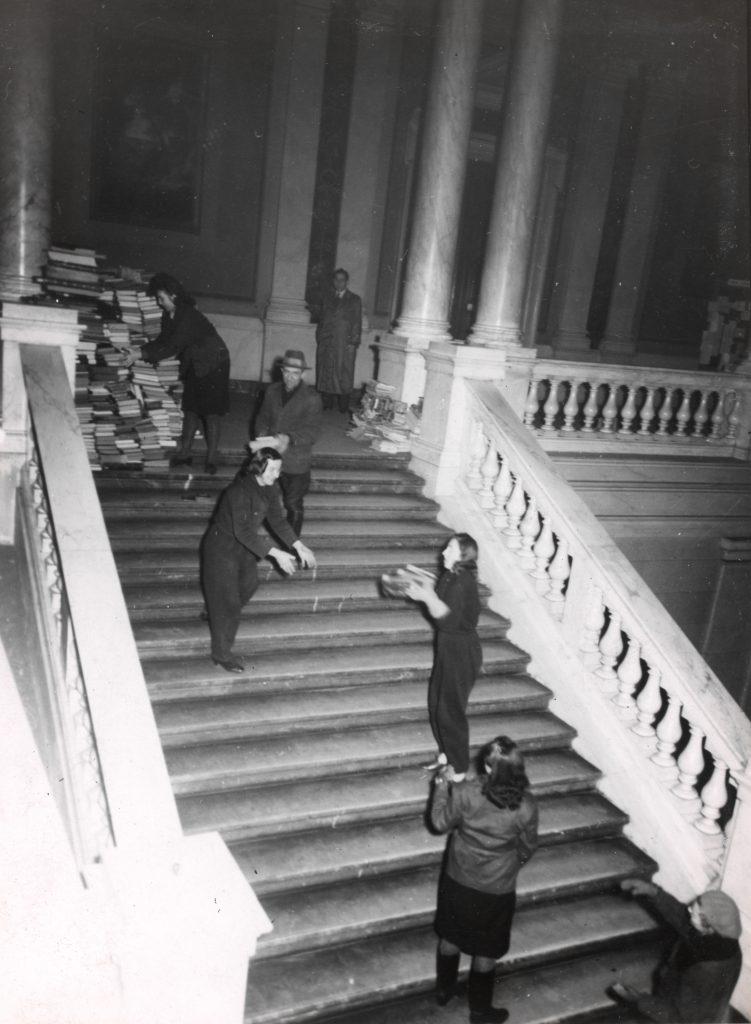 Schwarz-weiß: Eine Menschenkette befördert Bücher eine Treppe herauf zu einem großen Stapel.