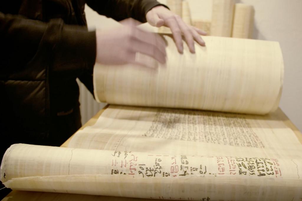 Zwei Hände rollen den Papyrus Ebers aus.